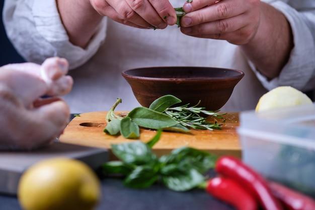 男は賢者を皿に入れます。オーブンでスパイスとレモンを使って鶏肉を調理するプロセス。