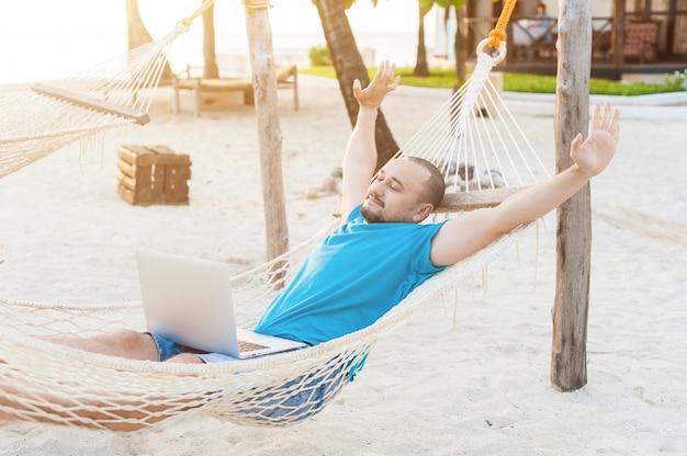 Мужчина довольно растягивается, лежа в гамаке с ноутбуком.