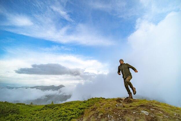 曇り空を背景に山を走る男