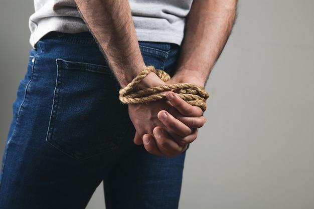 男の手はロープで結ばれています