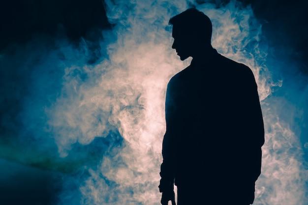 煙の中に立っている男のシルエット。夕方の夜