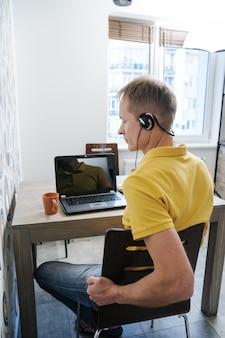 男はヘッドフォンで椅子に座っています。 Premium写真