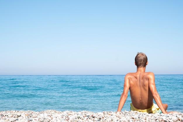 Мужчина сидит на берегу моря. концепция летних каникул. копировать пространство