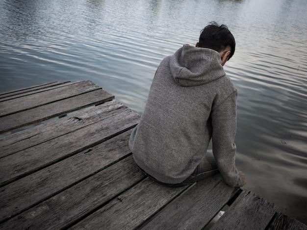 湖のそばの桟橋に座っている男。一人で、孤独、悲しい概念。