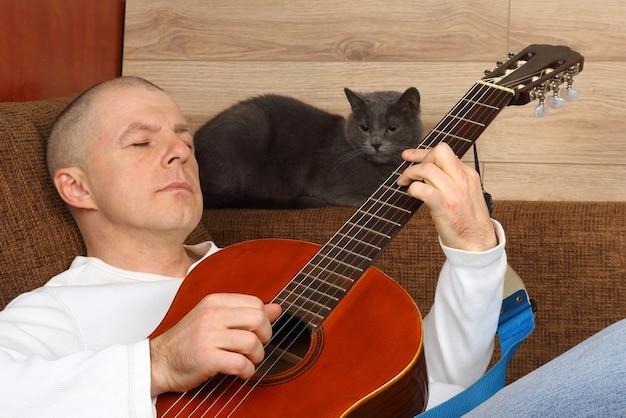 Мужчина сидит на диване с кошкой и играет на классической гитаре