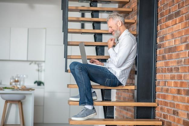 위층에 앉아서 노트북 작업을 하는 남자