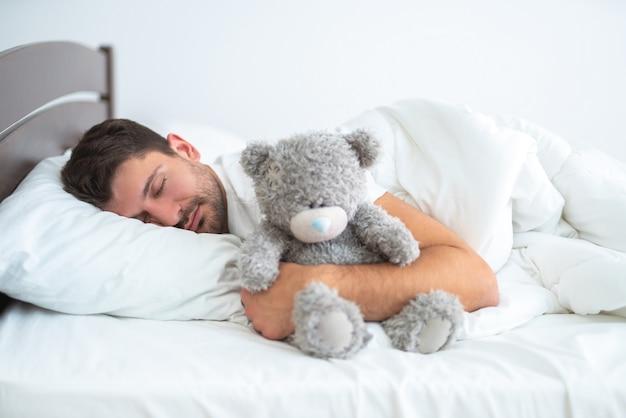 Человек спит с мягкой игрушкой на белом фоне