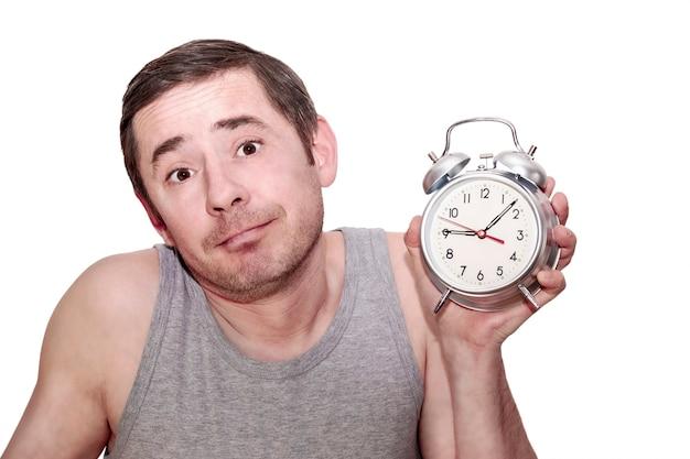 その男は仕事のために寝た。挙手した男が目覚まし時計を持っています。面白い表情。孤立した白い背景。