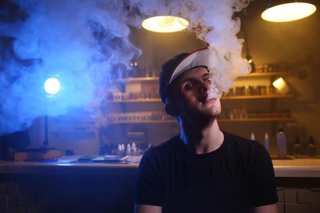 Мужчина курит электронную сигарету в магазине вейпов