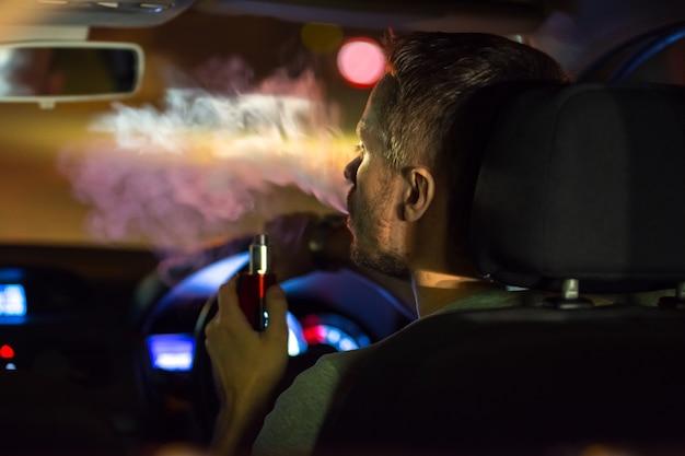 Мужчина курит в машине электронную сигарету. вечер в ночное время