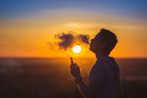 Мужчина курит электронную сигарету на фоне заката