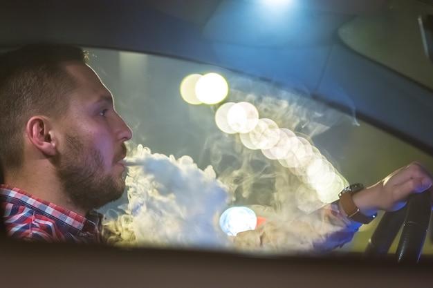 Мужчина курит электронную сигарету в машине. вечер ночное время
