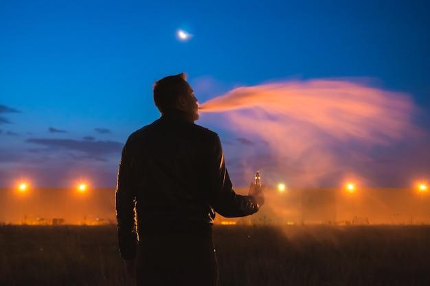 Мужчина курит электронную сигарету возле здания. вечер ночное время
