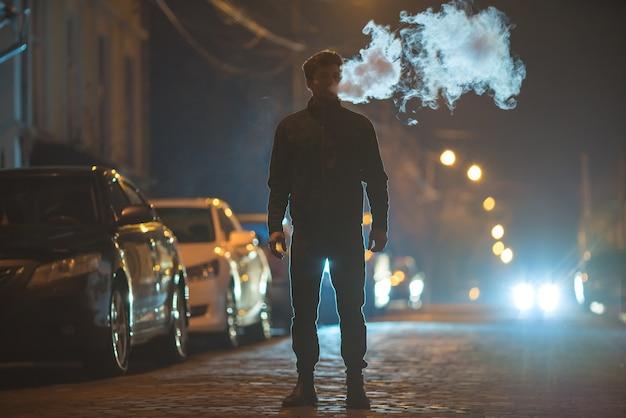 남자는 거리에서 담배를 피운다. 저녁 밤 시간입니다. 망원 렌즈 촬영