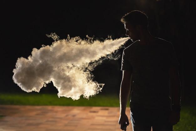 거리에서 담배를 피우는 남자. 저녁 밤 시간