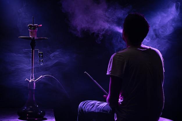 古典的なシーシャを吸う男。美しい色の光線と煙。水ギセル喫煙の概念。