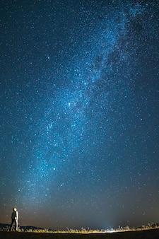 男は空の星の背景に立っています。夜の時間