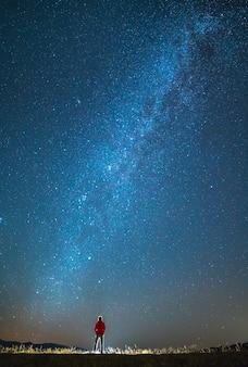 男は星の背景に立っています。夜の時間