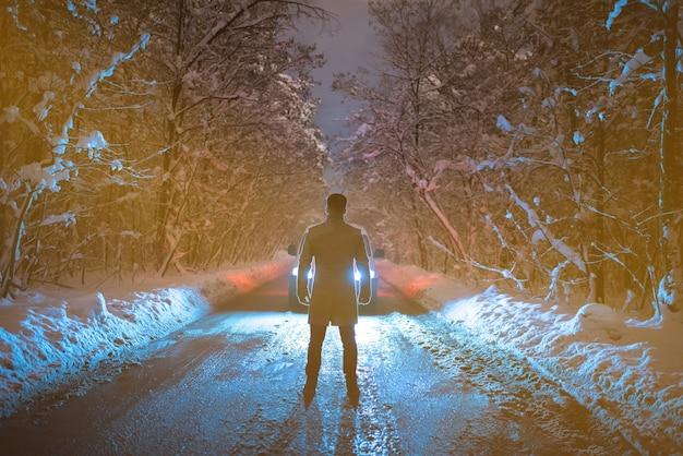 Мужчина противостоит автомобилю на лесной дороге. вечер ночное время
