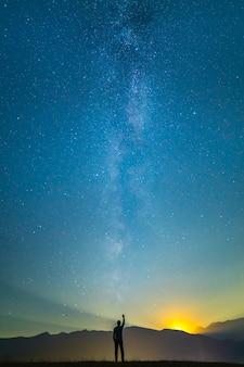 男は天の川の背景に立って身振りで示す。夜の時間