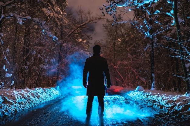 남자는 겨울 숲에서 푸른 연기 근처에 서 있습니다. 저녁 밤 시간