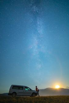 男は天の川の背景にある車の近くに立っています。夜の時間