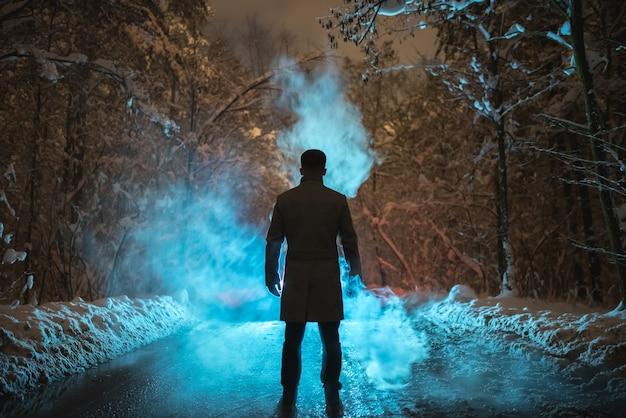 남자는 겨울 숲에서 연기 근처에 서 있습니다. 저녁 밤 시간
