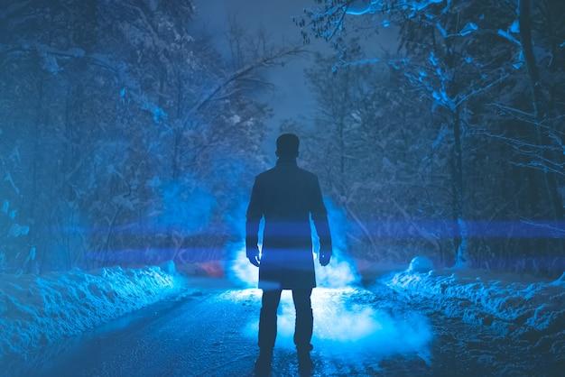 남자는 연기의 배경에 눈 덮인 길에 서 있습니다. 저녁 밤 시간