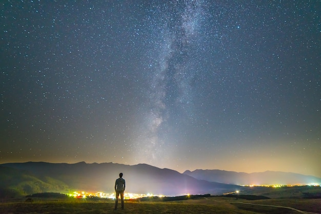 男は街の明かりの背景に立っています。夜の時間