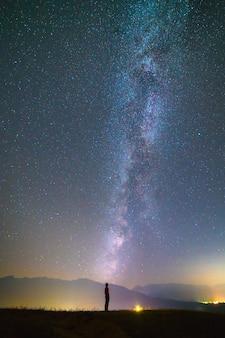 男は天の川の背景に立っています。夜の時間
