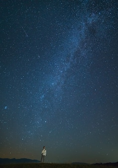 男は星空の背景に立っています。夜の時間