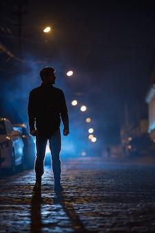 남자는 안개 낀 거리에 서 있다. 저녁 밤 시간입니다. 망원 렌즈 촬영