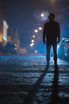 남자는 비 길에 서 있다. 저녁 밤 시간입니다. 망원 렌즈 촬영