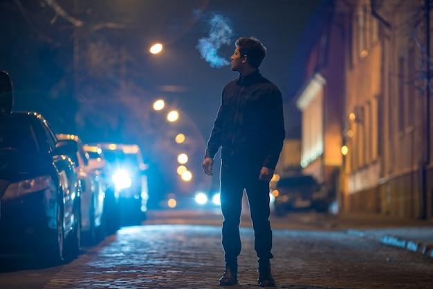 남자는 길에 서 있다. 저녁 밤 시간입니다. 망원 렌즈 촬영