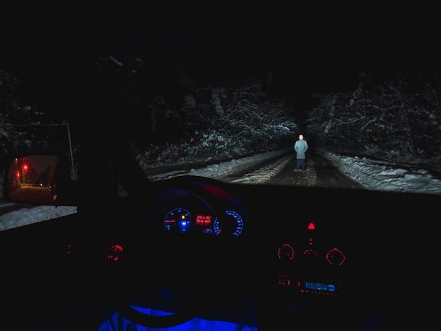 Мужчина стоит на заснеженной дороге возле машины. вид изнутри. вечер ночное время