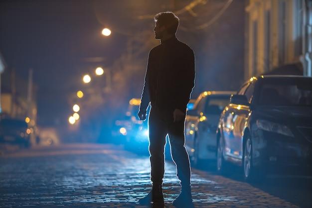 남자는 돌길에 서 있다. 저녁 밤 시간입니다. 망원 렌즈 촬영