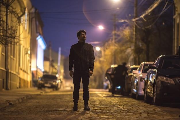 남자는 거리에 서 있다. 저녁 밤 시간입니다. 망원 렌즈 촬영