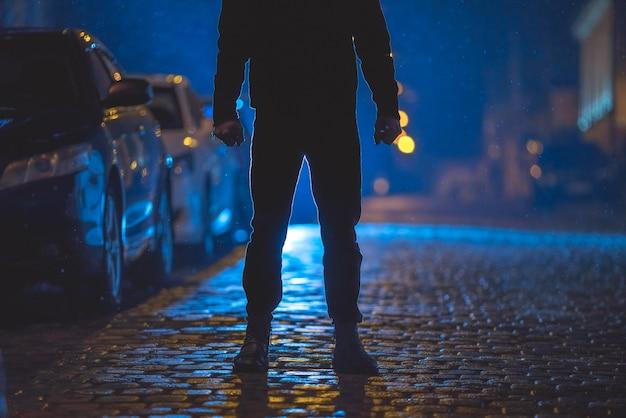 남자는 젖은 길에 서 있다. 저녁 밤 시간입니다. 망원 렌즈 촬영