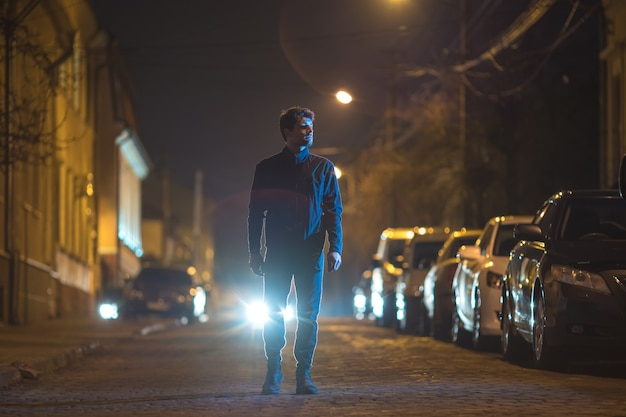 남자는 헤드라이트의 배경에 야외에 서 있다. 저녁 밤 시간