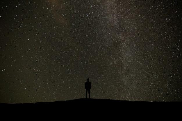 별이 있는 하늘 배경에 서 있는 남자