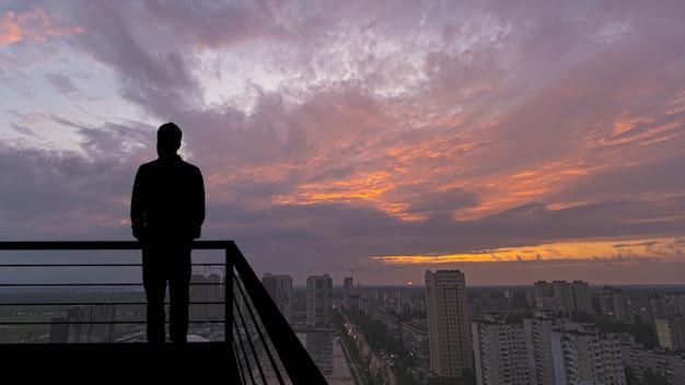 大都会の背景のバルコニーに立っている男