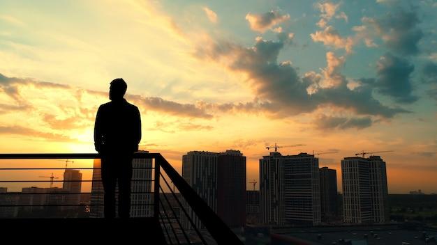 Человек, стоящий на балконе на фоне здания