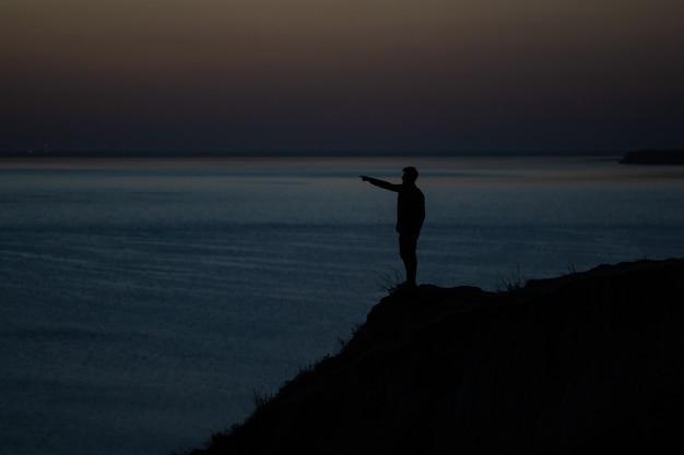 海の近くの山の端に立っている男