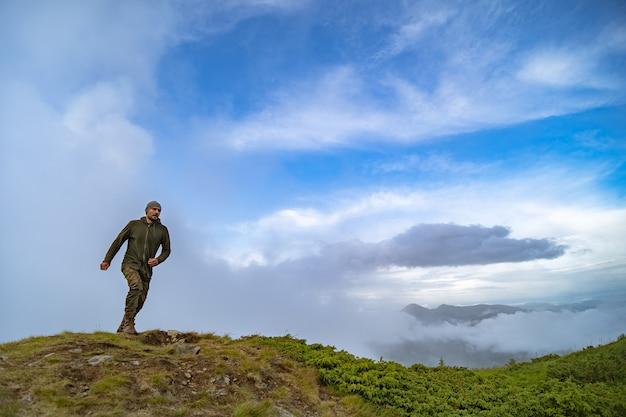 雲空の背景に山に立っている男