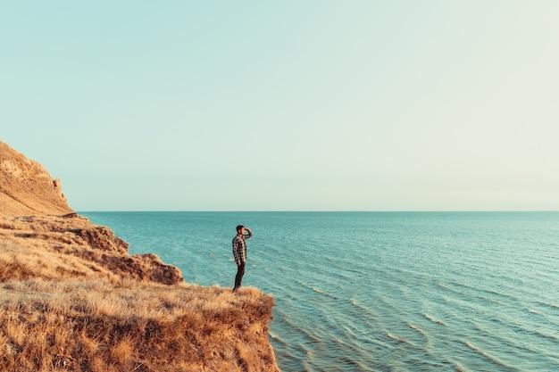 海の上の山の頂上に立っている男