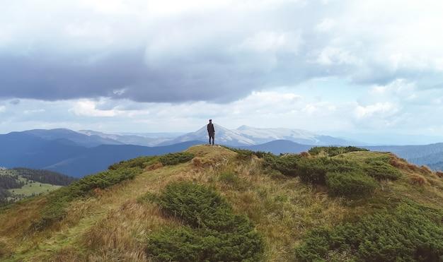 絵のように美しい山々の背景に立っている男