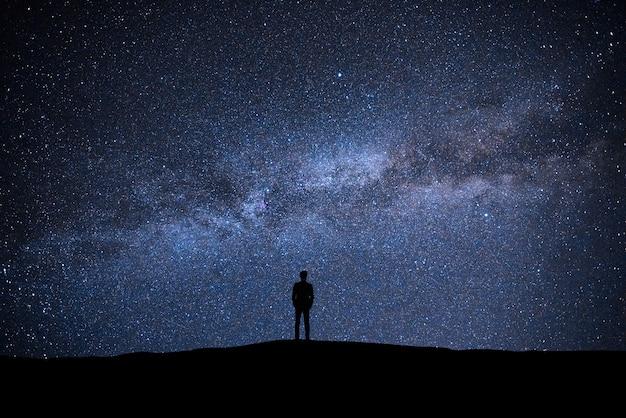그림 같은 별이 빛나는 하늘 배경에 서 있는 남자