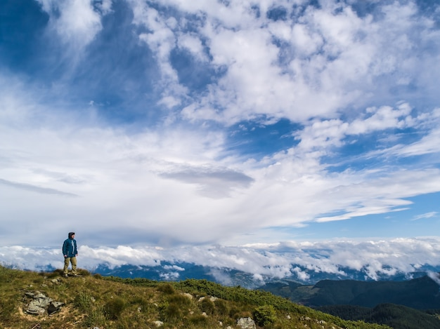 Человек, стоящий на скале против красивых облаков