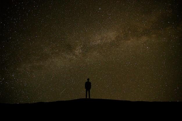별이 빛나는 하늘 배경에 서있는 남자