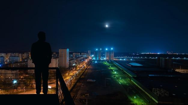 Человек, стоящий на вершине здания на фоне ночного городского пейзажа